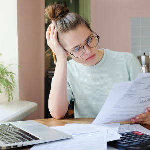 Woman sitting next to computer looking at financial bills.